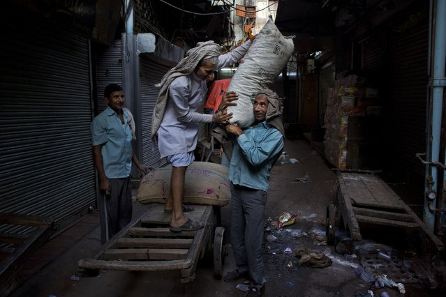 Indian laborers unload goods from a push cart in the morning at a spice market in the old Delhi area of New Delhi, India, Tuesday, April 14, 2015. The four-century-old neighborhood is chaotic and crowded, yet is the vibrant heart of the city. (Photo by Bernat Armangue/AP Photo)
