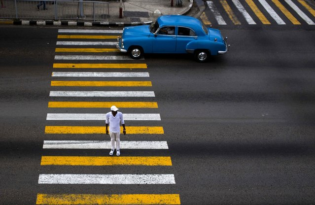 In this November 16, 2018 file photo, a man uses the cross walk where the drivers passes in his classic car in Havana, Cuba. (Photo by Desmond Boylan/AP Photo)