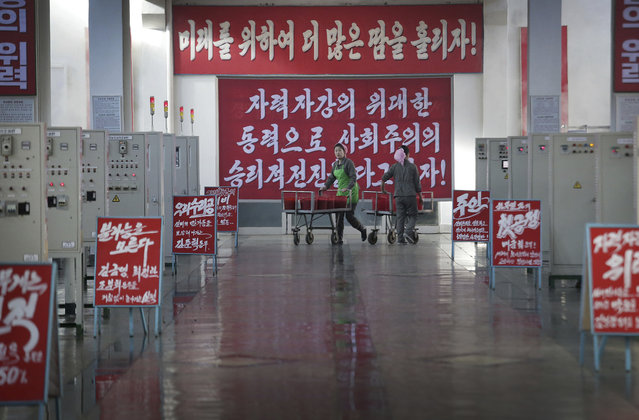"In this Friday, January 6, 2017, photo, North Korean women push trolleys along the aisles of the silkworm cocoon sorting and boiling hall at the Kim Jong Suk Silk Mill in Pyongyang, North Korea. The red-and-white sign carries the propaganda slogan: ""Let us step up the victorious advancement of socialism through self-development!"" Lining the walkway are the names of supervisors and workers that were leading teams, placed as a form of encouragement for the workers. (Photo by Wong Maye-E/AP Photo)"