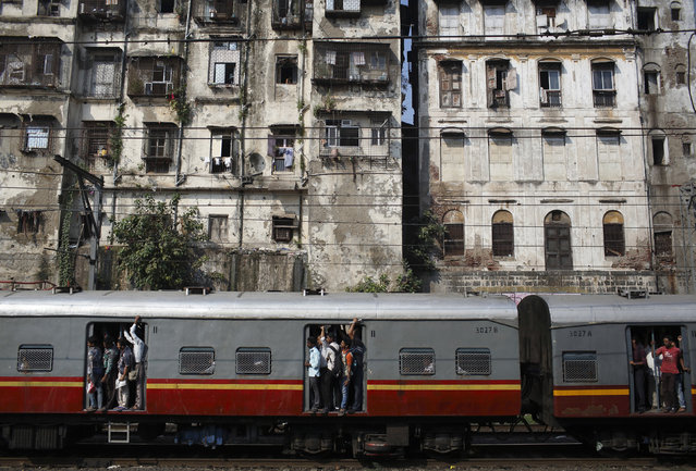 Commuters stand at the open doorways of a suburban train as they head toward their destination in Mumbai, November 3, 2012. (Photo by Navesh Chitrakar/Reuters)