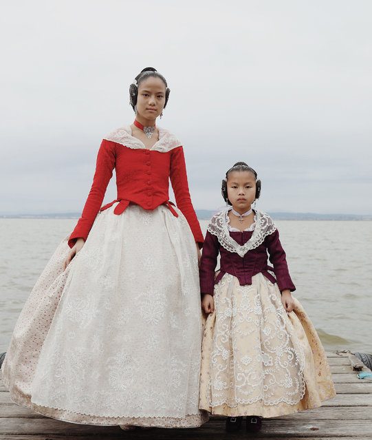 Portraits story nominee: Falleras, by Luisa Dörr. Fallera dresses for the Fallas de Valencia festival in Spain – inspired by clothes worn centuries ago by women working in rice fields - are now elaborate creations that can cost in excess of €1,000. Emma Xifeng Abril and Eva Lanhan Abril were adopted by the same parents and their adoptive mother, Maria, bought a piece of material from their country of birth to make these dresses. (Photo by Luisa Dörr/World Press Photo 2019)