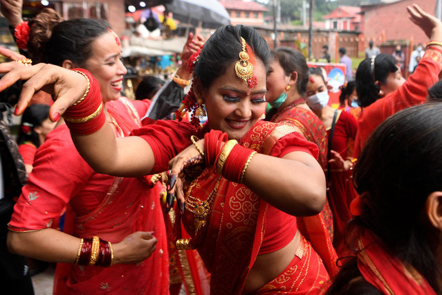 Hindu women dance after paying homage to Shiva, the Hindu god of destruction, as they celebrate the Teej festival outside the Pashupatinath temple, which is closed due to Covid-19 coronavirus pandemic, in Kathmandu on September 9, 2021. (Photo by Prakash Mathema/AFP Photo)