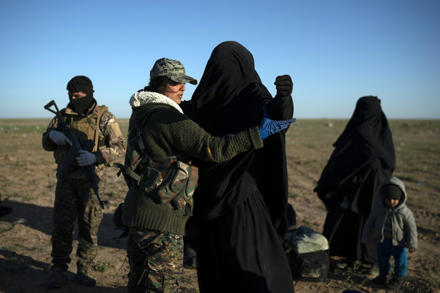 A woman is frisked by a U.S.-backed Syrian Democratic Forces (SDF) fighter at a screening area after being evacuated out of the last territory held by Islamic State militants, in the desert outside Baghouz, Syria, Friday, March 1, 2019. (Photo by Felipe Dana/AP Photo)