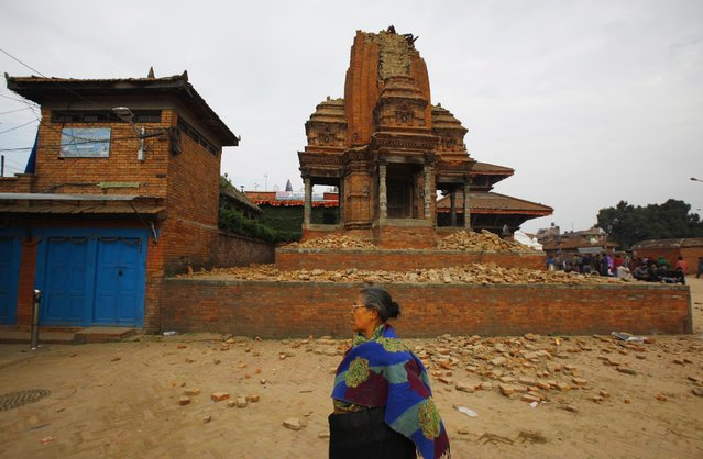 A Nepalese woman walks past a collapsed temple in Bhaktapur Durbar Square after an earthquake in Kathmandu, Nepal, Sunday, April 26, 2015. (Photo by Niranjan Shrestha/AP Photo)