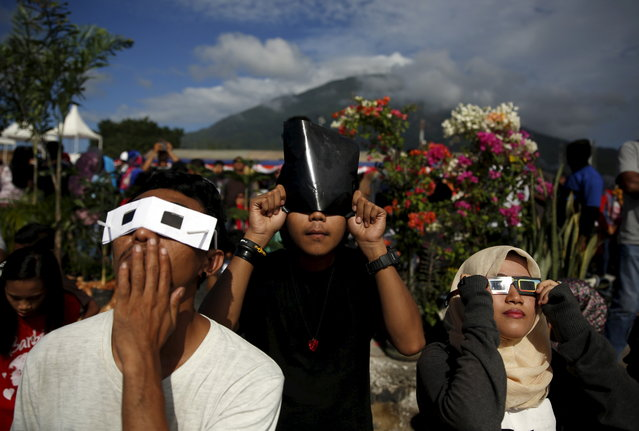 Youths watch a solar eclipse with self-made solar filters at the beach on Ternate island, Indonesia, March 9, 2016. (Photo by Reuters/Beawiharta)