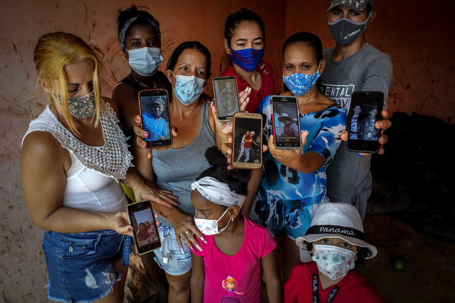 """Zuleydis """"Zuly"""" Elledias, left, shows a cellphone photo of her missing husband to a child while her neighbors pose for a group picture holding up cellphone photos of their missing relatives who ventured out in homemade boats in an attempt to reach Florida, in Orlando Nodarse, about 60 kilometers west of Havana, Cuba, Wednesday, June 30, 2021. Cuba is seeing a surge in unauthorized migration to the United States, fueled by an economic crisis. (Photo by Ramon Espinosa/AP Photo)"""