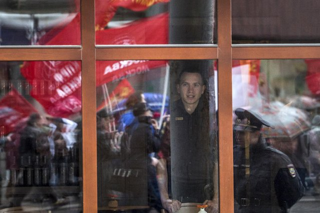 A restauramt waiter looks through a window reflecting communist demonstrators during a May Day demonstration in downtown Moscow, Russia, Friday, May 1, 2015. As in Soviet times, tens of thousands of cheerful workers paraded across Red Square despite a chilly rain, but instead of red flags with the Communist hammer and sickle, they waved the blue flags of the dominant Kremlin party and the Russian tricolor. (Photo by Denis Tyrin/AP Photo)