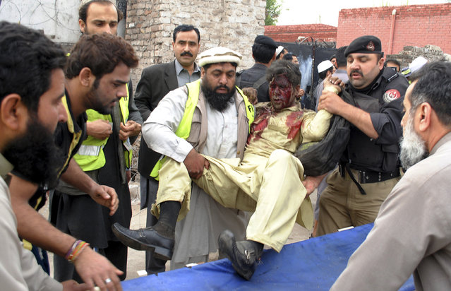 Pakistani volunteers carry an injured passenger following a bomb blast in Peshawar, Pakistan, Wednesday, March 16, 2016. A bomb ripped through a bus carrying Pakistani government employees in the northwestern city of Peshawar on Wednesday, killing a number of people, police said. (Photo by Mohammad Sajjad/AP Photo)