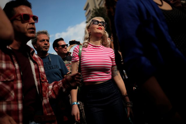A woman dressed in a fifties-style outfit stands as she listens a concert during the 23rd Rockin' Race Jamboree International Festival in downtown Torremolinos, near Malaga, southern Spain February 4, 2017. (Photo by Jon Nazca/Reuters)