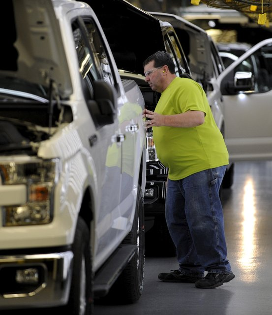 Auto worker Jim Hamilton looks for imperfections on a completed Ford F150 pickup at the Kansas City Assembly Plant where new aluminum intensive Ford F-Series pickup is built in Claycomo, Missouri May 5, 2015. (Photo by Dave Kaup/Reuters)