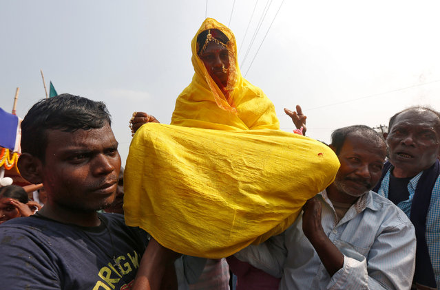 Relatives carry a bride on their shoulders as part of a ritual during a mass marriage ceremony in which, according to its organizers, 109 tribal, Muslim and Hindu couples from various villages across the state took their wedding vows, at Bahirkhand village, north of Kolkata, February 5, 2017. (Photo by Rupak De Chowdhuri/Reuters)