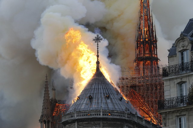 Flames burn the roof of the landmark Notre-Dame Cathedral in central Paris on April 15, 2019, potentially involving renovation works being carried out at the site, the fire service said. A major fire broke out at the landmark Notre-Dame Cathedral in central Paris sending flames and huge clouds of grey smoke billowing into the sky, the fire service said. The flames and smoke plumed from the spire and roof of the gothic cathedral, visited by millions of people a year, where renovations are currently underway. (Photo by Francois Guillot/AFP Photo)