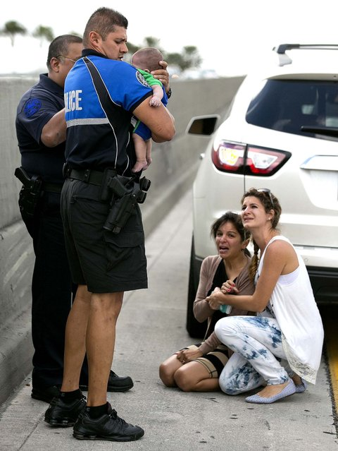 Sweetwater officer Amauris Bastidas helps with the rescue of de la Cruz, who had stopped breathing. Lucila Godoy, who stopped her car to assist in the rescue, comforts de la Cruz's aunt, Pamela Rauseo. (Photo by Al Diaz/Miami Herald/MCT)