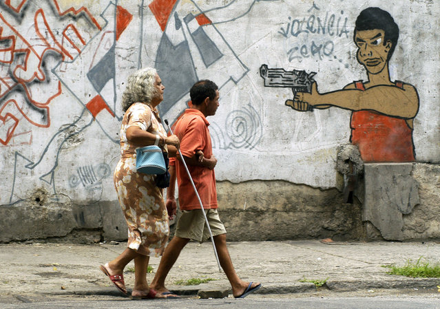 In this October 22, 2005 file photo, people walk past graffiti in Rio de Janeiro, Brazil, a day before a vote to ban the sale of firearms and ammunition to civilians. Backed by the Roman Catholic church and other powerful forces in the country, one poll a month before the referendum put support at 73 percent. The U.S.-based National Rifle Association worked with activists in Brazil to help defeat it. (Photo by Renzo Gostoli/AP Photo/File)