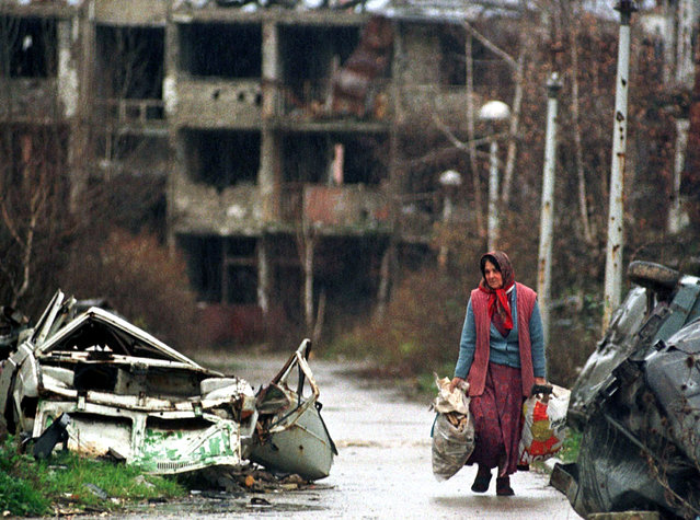 An elderly woman carries her belongings in Sarajevo's war shattered airport settlement, November 1995. (Photo by Reuters)