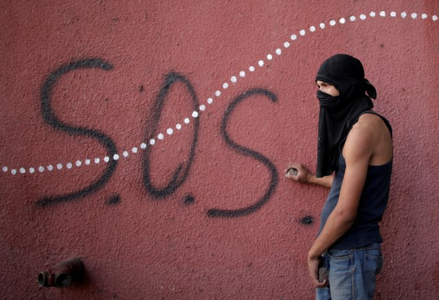 An opposition supporter holds rocks during clashes with security forces following a rally against the government of Venezuela's President Nicolas Maduro and to commemorate May Day in Caracas, May 1, 2019. (Photo by Ueslei Marcelino/Reuters)