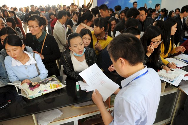 People line up to apply for teaching jobs at the local education bureau, in Lianyungang, Jiangsu province, China, May 6, 2015. (Photo by Reuters/China Daily)
