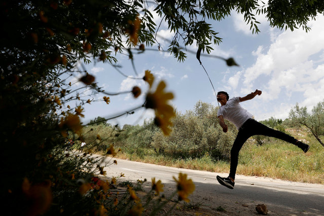 A Palestinian hurls stones at Israeli troops during clashes at a protest against Jewish settlements, near Ramallah in the Israeli-occupied West Bank on May 3, 2019. (Photo by Mohamad Torokman/Reuters)