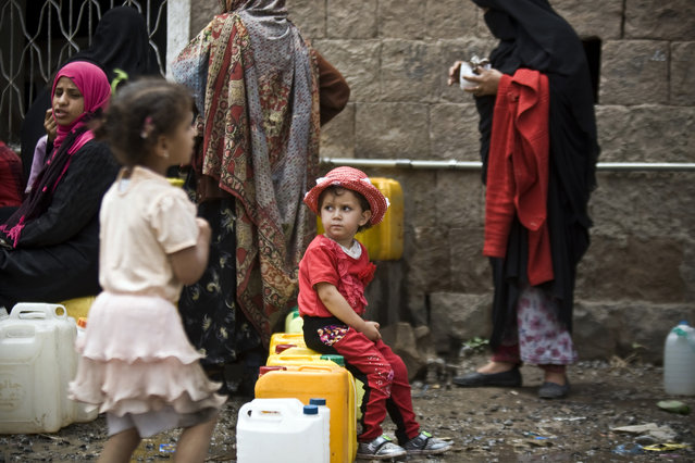 A girl waits for her turn to fill buckets with water from a public tap amid an acute shortage of water, in Sanaa, Yemen, Saturday, May 9, 2015. (Photo by Hani Mohammed/AP Photo)