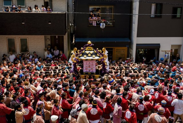 Revellers carry a portable shrine, a Mikoshi, through a narrow street  during the Sanja Matsuri festival in the Asakusa district of Tokyo May 17, 2015. (Photo by Thomas Peter/Reuters)