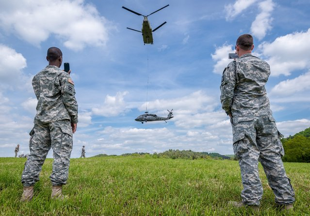 US Army soldiers use their smart phones to film the recovery of a Sikorsky UH-60 Black Hawk helicopter (bottom) by a Boeing CH-47 Chinook helicopter (top) in Plankenfels, Germany, 18 May 2015. The pilots had to make an emergency landing on a meadow near Plankenfels on 15 May, after a power line was overlooked. The main rotor of the helicopter severed one of the power lines and was damaged during the process. (Photo by Nicolas Armer/EPA)