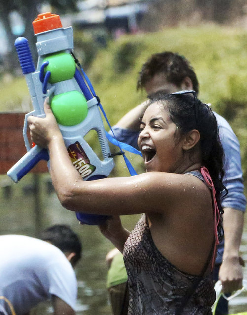 In this April 13, 2014 file photo, a foreign tourist holds a water gun as she takes part in a water fight during traditional Thai New Year celebrations or Songkran festival in Chiang Mai province, northern Thailand. Thailand's military government is putting a dampener on the annual nationwide water fight. Despite Thailand's worst drought in 20 years, the junta says it has no intention of limiting the virtually around-the-clock water throwing that defines the three-day Songkran festival. Instead, it has decided to impose morality measures. (Photo by Apichart Weerawong/AP Photo)