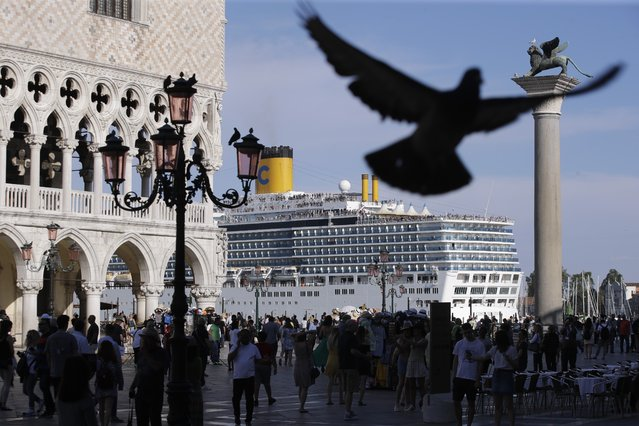 A cruise ship passes by St. Mark's Square filled with tourists, in Venice, Italy, Sunday, June 2, 2019. Groups that want to ban cruise ships on Venice's busy canals say a collision that injured four tourists has served as a wake-up call. Opponents say cruise ships are out-of-scale for Venice, cause pollution, threaten the lagoon's ecosystem and dangerous. (Photo by Luca Bruno/AP Photo)