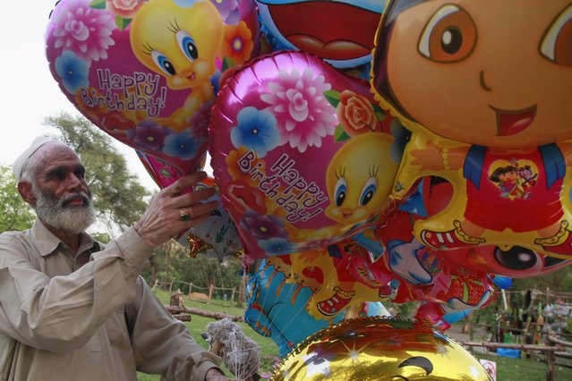 A balloon seller unties a balloon outside a zoo in Islamabad April 21, 2015. (Photo by Sara Farid/Reuters)