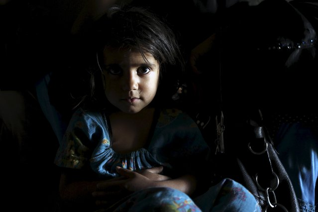 A girl looks on while resting on her mother's lap as they sit inside an underground water tunnel with other displaced Yemeni families, after they were forced to flee their home due to ongoing air-strikes carried out by the Saudi-led coalition in Sanaa May 2, 2015. (Photo by Mohamed al-Sayaghi/Reuters)