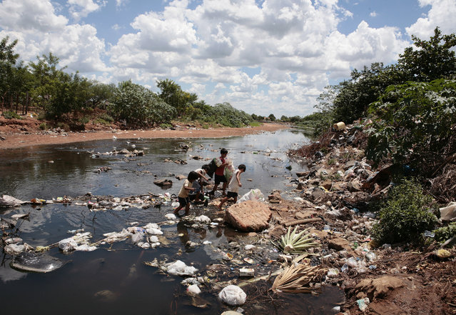 Children cross a garbage-filled tributary of the Paraguay River in Asuncion February 10, 2010. Temperatures soared to nearly 40 degrees Celsius (104 degrees Fahrenheit) as a heat wave caused electricity transformers to overheat, blacking out parts of the country and causing water shortages when city pumps shut down. (Photo by Jorge Adorno/Reuters)