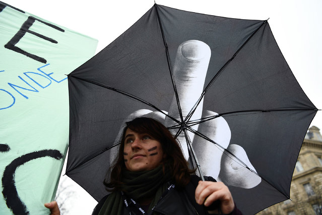 A woman holds an umbrella during a demonstration for the International Women's Day in Paris on March 8, 2017. (Photo by Gabriel Bouys/AFP Photo)