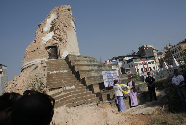 Volunteers hold a wreath as they await the arrival of Nepal's Prime Minister Khadga Prasad Oli, at the ruins of the Dharahara tower in the heart of Kathmandu, Nepal, Sunday, April 24, 2016. Government officials, diplomats and ordinary people gathered at the remains of the fallen iconic tower in the Nepalese capital on Sunday to mark the anniversary of a devastating earthquake that killed thousands and injured many more in the Himalayan nation. (Photo by Niranjan Shrestha/AP Photo)