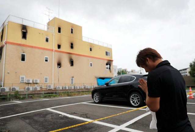 """A man prays for the victims of the arson attack in front of the torched Kyoto Animation building n Kyoto, Japan, July 19, 2019. On the morning of 18th, a fire occurred with an explosion sound at a studio of an animation production company """"Kyoto Animation"""" in Fushimi Ward, Kyoto City. 34 staffs died, and 34 staffs were injured as of 19th. Shinji Aoba, the 41-year-old man who allegedly splashed gasoline in the building while screaming """"Die!"""" reportedly said. """"They stole my idea"""" when he was taken by police. Kyoto Animation produced poplar animations such as """"K-On!"""", """"The Melancholy of Haruhi Suzumiya"""" and """"Sound! Euphonium"""". (Photo by Kim Kyung-Hoon/Reuters)"""