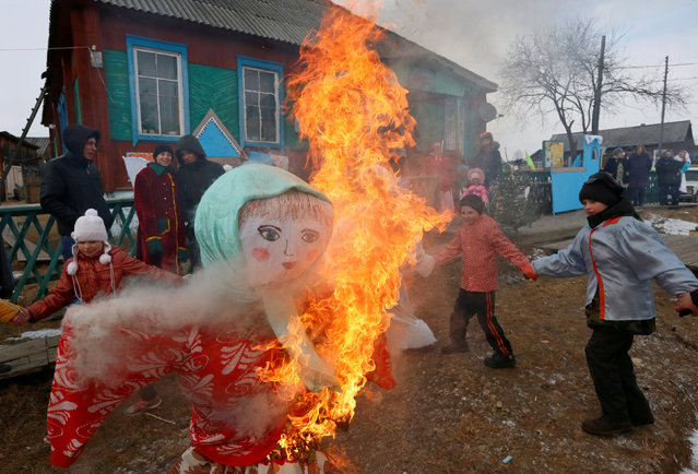 People take part in celebrations of Maslenitsa, also known as Pancake Week, which is a pagan holiday marking the end of winter, in a street of a Siberian settlement founded as a logging camp and part of the Soviet Union's Gulag prison labour system, Tugach, southeast of Krasnoyarsk, March 10, 2019. (Photo by Ilya Naymushin/Reuters)