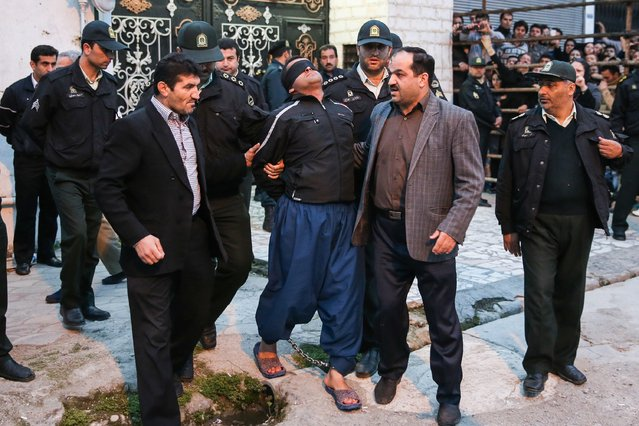 Balal (C), who killed an Iranian youth Abdolah Hosseinzadeh in a street fight with a knife in 2007, is brought to the gallows by judicial officals during his execution ceremony in the northern city of Nowshahr on April 15, 2014. Samereh Alinejad, the mother of the victim, spared the life of Balal, her son's convicted murderer, with an emotional slap in the face as he awaited execution prior to removing the noose around his neck. (Photo by Araash Khamooshi/AFP Photo/ISNA)