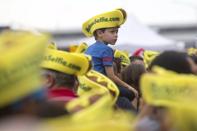 A boy wearing a hot dog hat is seen in the crowd before the annual Fourth of July 2015 Nathan's Famous Hot Dog Eating Contest in Brooklyn, New York July 4, 2015. (Photo by Andrew Kelly/Reuters)