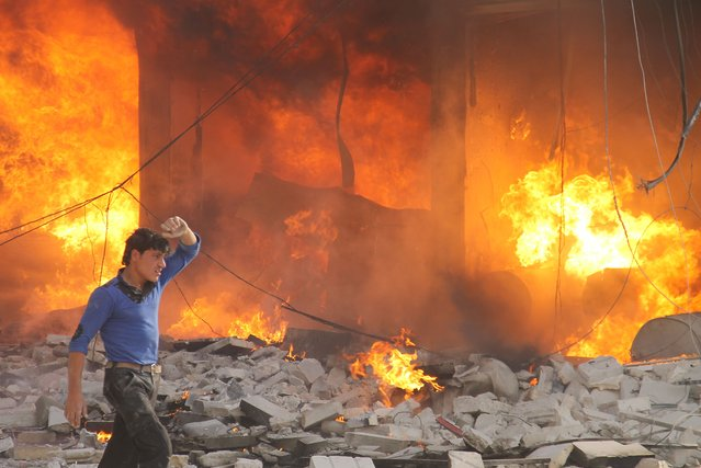 A man walks past a burning building following a reported air strike by pro-regime forces on the northern Syrian city of Aleppo, on April 24, 2014. (Photo by Khaled Khatib/AFP Photo/AMC)