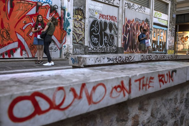 """In this Friday, July 26, 2019 photo, a marble-topped wall round the 11th Century AD Panagia Kapnikarea church and a shop that has been closed for months are covered with graffiti in Athens' Ermou main shopping street.While Athens has acquired many striking murals by artists commissioned by public bodies or private property owners, most of the new graffiti is unsolicited, devoid of visible meaning and cacophonous – a jostling mass of individual """"look at me"""" cries on somebody else's wall. (Photo by Petros Giannakouris/AP Photo)"""