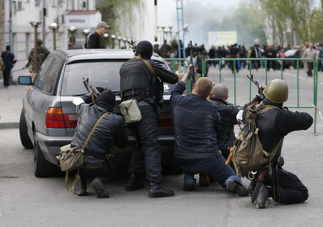 Pro-Russian armed men take cover behind a car near the local police headquarters in Luhansk, eastern Ukraine, April 29, 2014. Pro-Russian separatists in Ukraine opened fire with automatic weapons and threw stun grenades at the local police headquarters in the eastern city of Luhansk on Tuesday, a Reuters photographer said. (Photo by Vasily Fedosenko/Reuters)