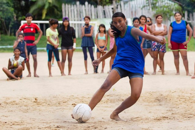 An Amazon Indian girl kicks the ball during a soccer match between various ethnic groups of indigenous communities in Nossa Senhora do Livramento, a rural community on the outskirts of Manaus, Brazil, on March 29, 2014. (Photo by Bruno Kelly/Reuters)