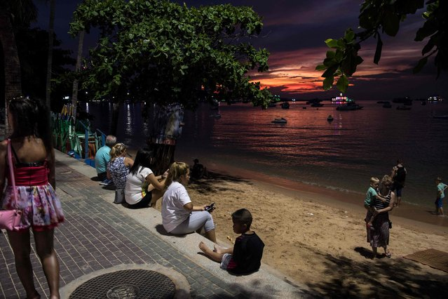 This photo taken on March 29, 2017 shows a woman (L) walking past tourists and residents watching the sunset in Pattaya. (Photo by Roberto Schmidt/AFP Photo)