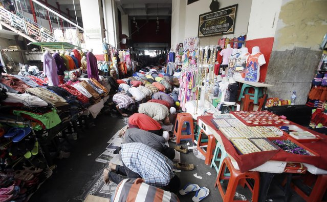 Indonesian Muslims pray during a Friday prayer at a market in Jakarta, Indonesia, Friday, July 10, 2015. During Ramadan, Muslims refrain from eating, drinking, smoking and s*x from dawn to dusk. (Photo by Achmad Ibrahim/AP Photo)