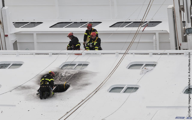 Rescuers work on the cruise ship Costa Concordia as lies stricken off the shore of the island of Giglio