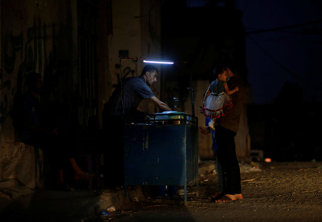 A Palestinian man sells falafel as he uses a battery-powered light during power cut in the northern Gaza Strip on August 26, 2019. (Photo by Mohammed Salem/Reuters)