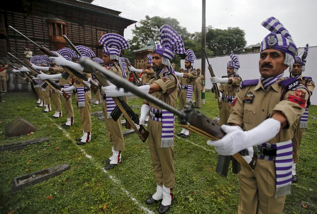 """Indian policemen in ceremonial attire perform during an event at martyrs graveyard to mark """"Martyrs Day"""" in Srinagar July 13, 2015. (Photo by Danish Ismail/Reuters)"""