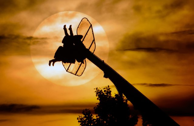A fairground ride is silhouetted against the setting sun at the Spring Festival in Hanover, Germany, 05 May 2014.  (Photo by Julian Stratenschulte/EPA)