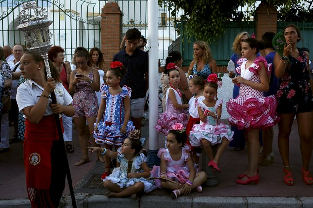 Girls, wearing traditional sevillana dresses, watch the procession of the El Carmen Virgin, on its way to be carried into the sea, in Malaga July 16, 2015. (Photo by Jon Nazca/Reuters)