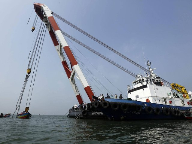 Rescue operations are undergoing to recover the sunken ferry MV Miraj 4 in the Megna River near Munshiganj, Bangladesh, 16 May 2014. The death toll in the Bangladesh ferry disaster rose to 26 on 16 May, including children and women and many more feared dead as the ferry, carrying more than 200 passengers on board, sunk during a storm on 15 may 2014, police authorities said. (Photo by Abir Abdullah/EPA)