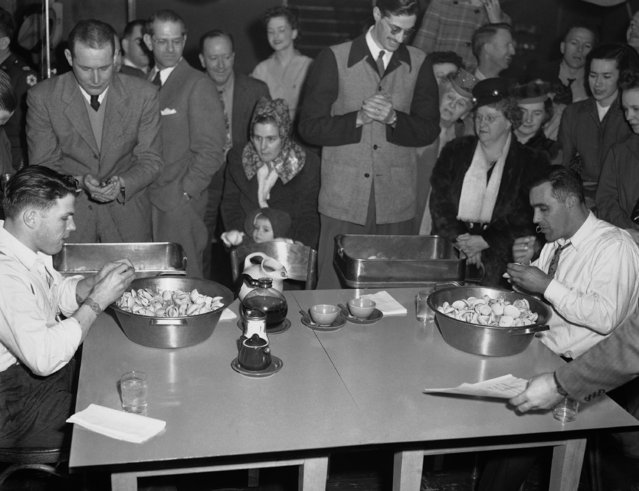 """Dick Watson, left, consuming 132 clams in ten minutes during a """"Clam Bowl"""" gulping contest, beats Joe Silva, right, of Martha's Vineyard, Mass., who ate 127 in the same space of time in Seattle, Wash., January 24, 1948. A time-keeper, left standing, keeps an eye on the clock as others watch the event. (Photo by AP Photo)"""