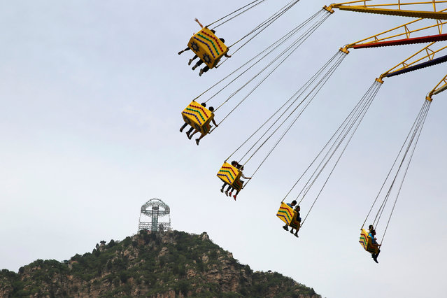 The glass sightseeing platform on Shilin Gorge is seen over a ride at an amusement park in Beijing, China, May 27, 2016. (Photo by Kim Kyung-Hoon/Reuters)